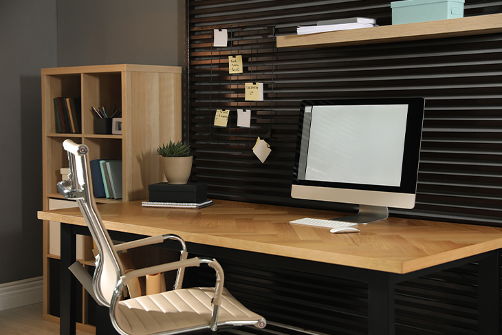 Workplace with office chair and computer on wooden table