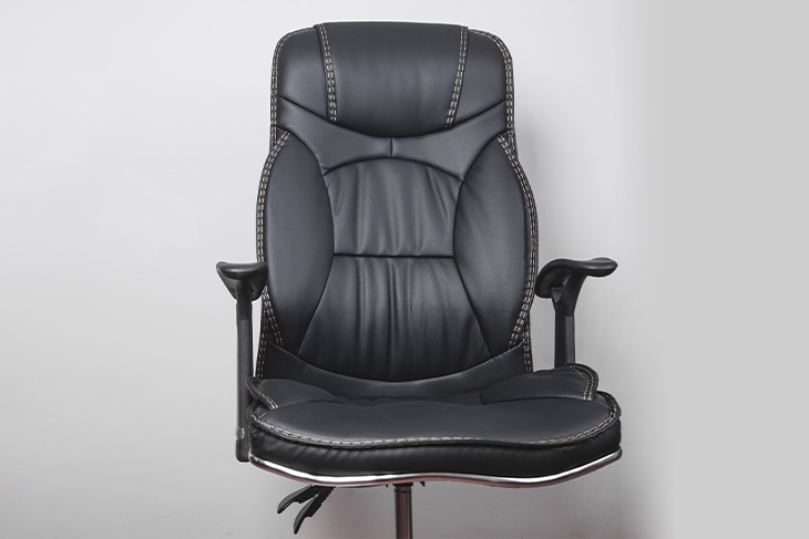 Black leather office chair in a grey background.