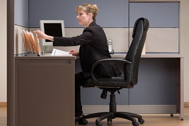 Businesswoman sitting in cubicle and reviewing paperwork